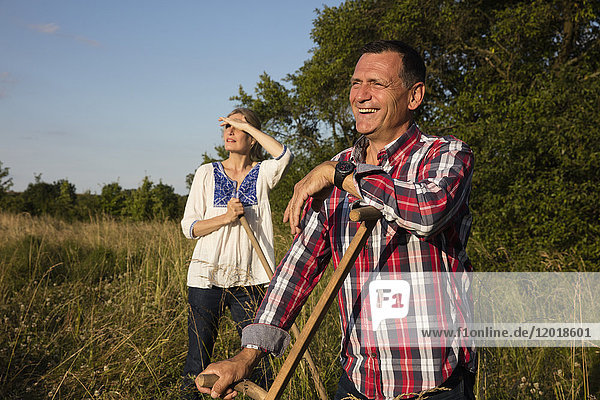 Lächelndes reifes Paar mit Ausrüstung  das an einem sonnigen Tag auf dem Bauernhof steht.