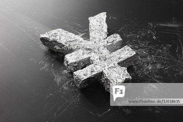 Hochwinkelansicht des Betonwährungssymbols auf schwarzem Tisch