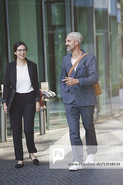 Fröhliche Geschäftsleute beim Spazierengehen auf dem Bürgersteig in der Stadt