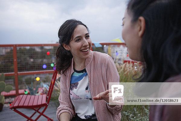 Fröhliche Frau im Gespräch mit einer Freundin auf der Terrasse
