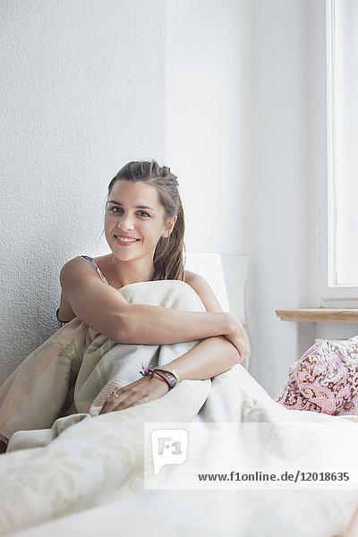 Porträt einer schönen Frau  die zu Hause mit Decke auf dem Bett sitzt.