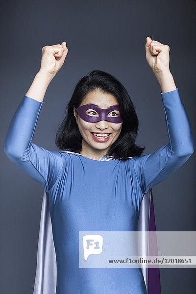 Porträt einer aufgeregten weiblichen Superheldin mit erhobenen Armen auf grauem Hintergrund