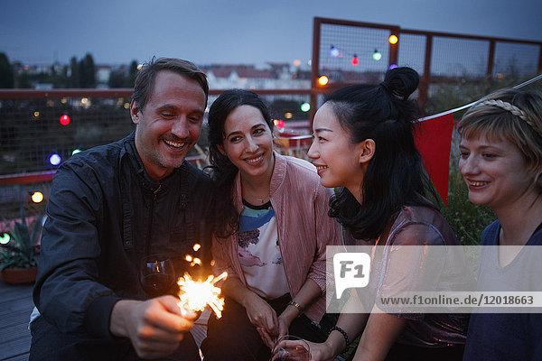 Glücklicher Mann  der nachts mit weiblichen Freunden die Wunderkerze in der Hand hält.
