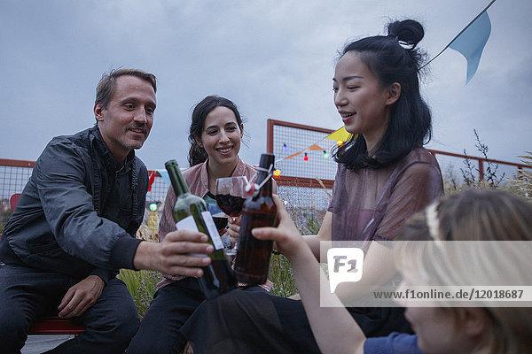 Multi-ethnische Freunde toasten Weinflaschen während der Party auf der Terrasse