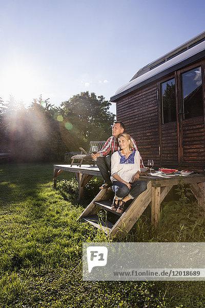 Ein reifes Paar  das sich bei einem Wein im Freien bei Sonnenschein entspannen kann.