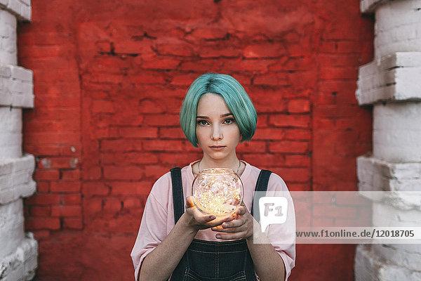 Porträt eines jungen Mädchens  das beleuchtete Lichterketten hält  während es an der Ziegelwand steht. Porträt eines jungen Mädchens, das beleuchtete Lichterketten hält, während es an der Ziegelwand steht.