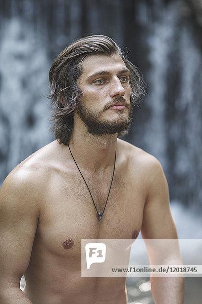 Nachdenklicher junger Mann ohne Hemd  der weg schaut  während er gegen den Wasserfall im Wald steht.