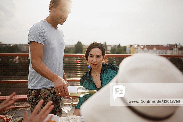 Mann serviert Weißwein an Freundin während der Party auf der Terrasse
