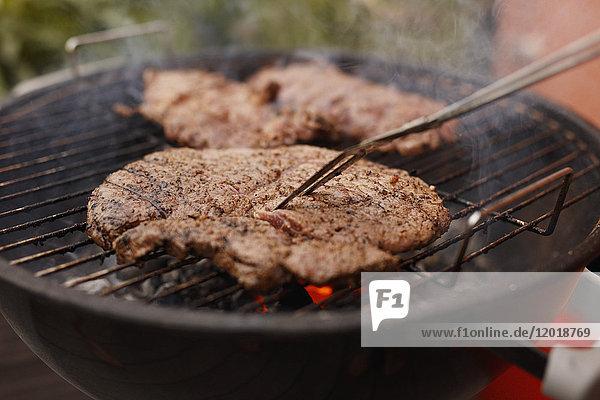 Nahaufnahme des Steaks beim Grillen auf der Terrasse