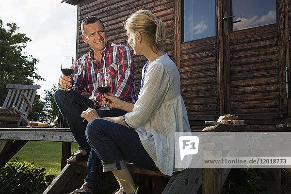 Tiefblick auf ein reifes Paar  das außerhalb des Bauernhauses redet und Wein trinkt.