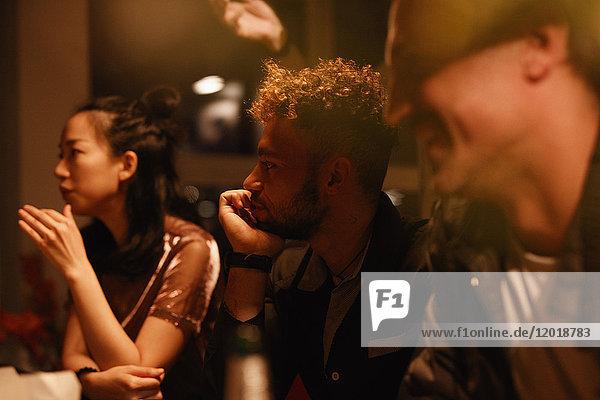 Männliche und weibliche Freunde  die sich während der Party zu Hause unterhalten.
