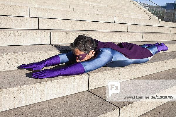 Seitenansicht des als Superheld gekleideten Mannes auf einer Treppe liegend