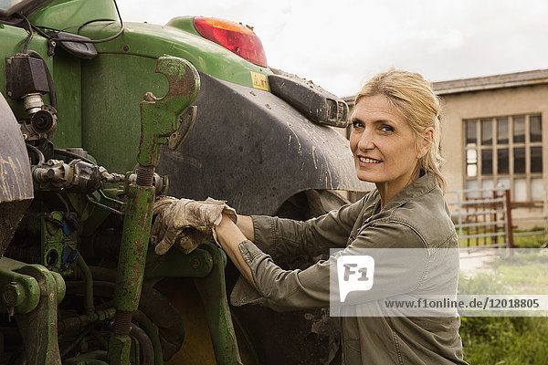 Porträt einer lächelnden Bäuerin  die an Landmaschinen gegen den Himmel steht