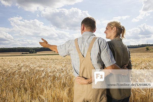 Rückansicht des Paares  das am Weizenfeld gegen den Himmel steht