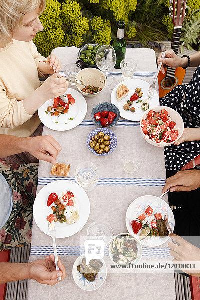 Direkt über der Aufnahme von männlichen und weiblichen Freunden beim Mittagessen am Außentisch