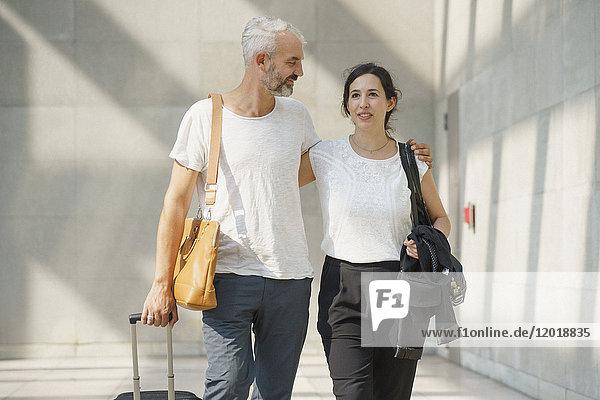 Paar mit Rollgepäck zu Fuß am Flughafen
