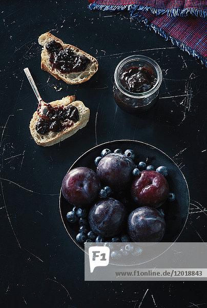 Direkt über dem Schuss von Früchten mit offenem Sandwich und Konserven auf Granit