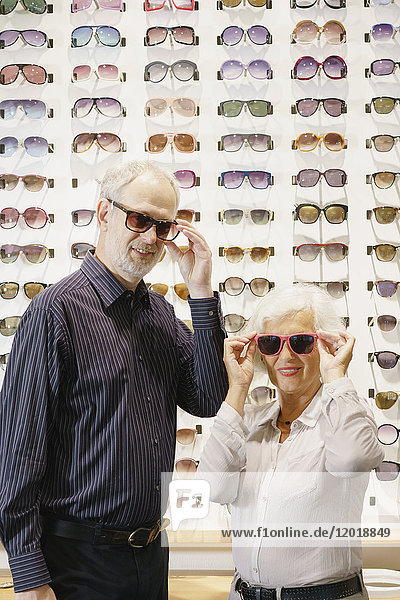 Porträt eines lächelnden Mannes und einer lächelnden Frau mit Sonnenbrille im Laden.