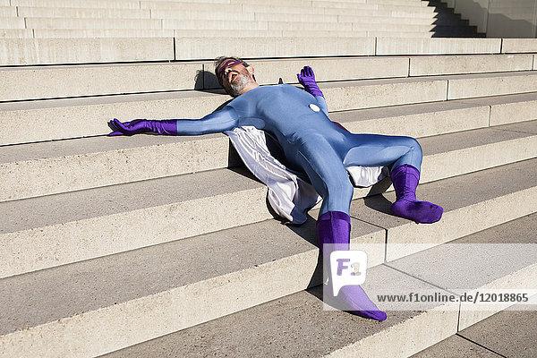 Mann als Superheld verkleidet auf einer Treppe liegend