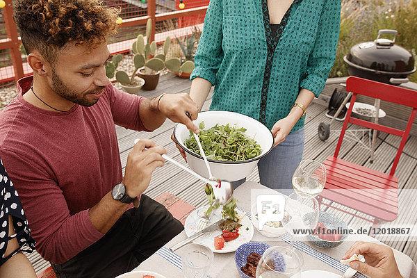 Hochwinkelansicht des Mannes  der Salat im Teller auf der Terrasse serviert.