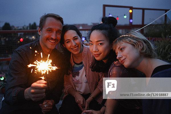Porträt eines glücklichen Mannes mit Wunderkerze  der nachts mit Freundinnen zusammensitzt