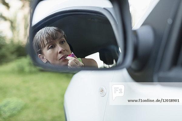 Frau mit Lippenstift beim Blick auf den Seitenspiegel des Autos