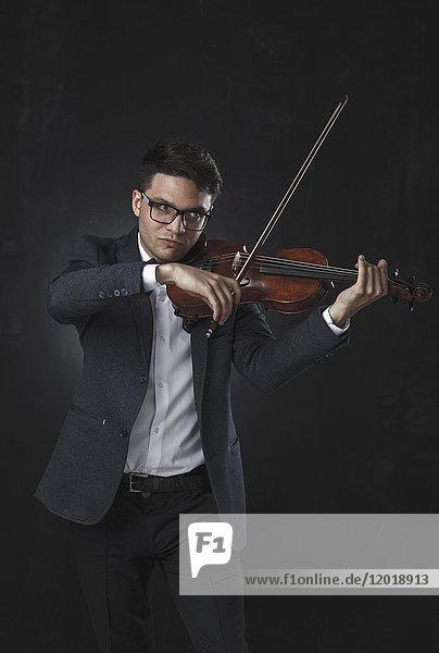 Sicherer Musiker beim Geigenspiel vor schwarzem Hintergrund
