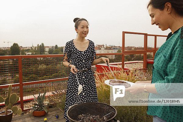 Lächelnde Frau serviert frisch gegrilltes Steak an Freundin auf der Terrasse