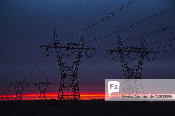 Silhouette Strommasten auf dem Feld gegen den Himmel in der Dämmerung