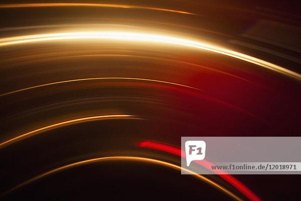Abstraktes Bild lebendiger Lichtspuren vor schwarzem Hintergrund