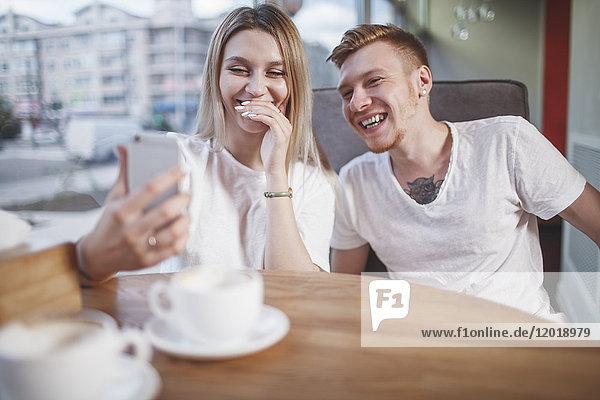 Glückliches junges Paar  das im Restaurant auf sein Handy schaut.