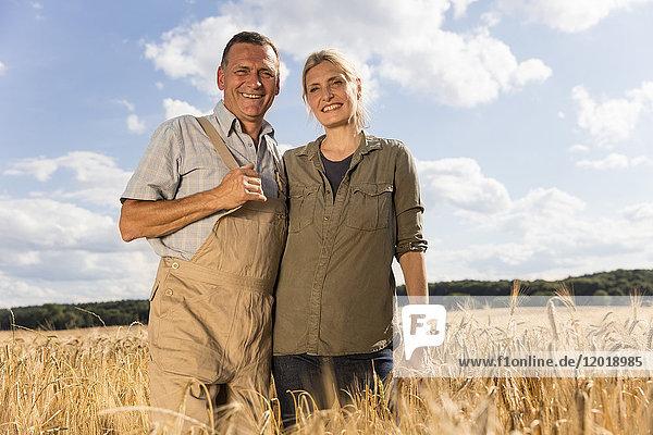 Flachwinkel-Porträt eines lächelnden reifen Paares  das auf dem Bauernhof gegen den Himmel steht
