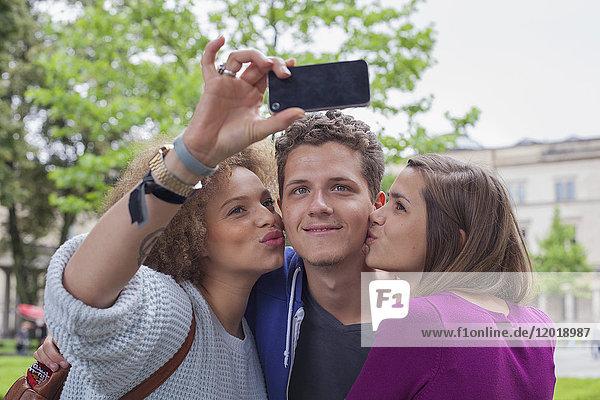 Frau nimmt Selfie mit einer Freundin  während sie einen jungen Mann küsst.