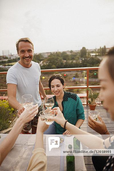 Fröhliche Freunde rösten Weingläser am Außentisch auf der Terrasse.