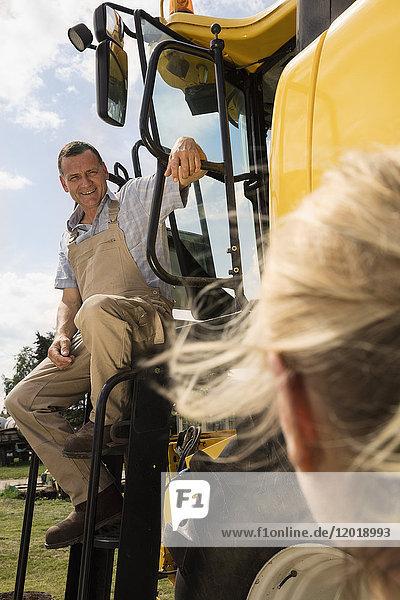 Erwachsener Mann im Gespräch mit einer Frau,  während er auf dem Traktor auf dem Bauernhof sitzt.
