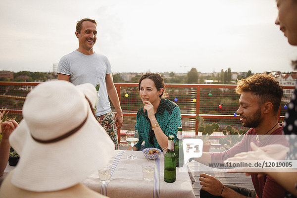 Glückliche männliche und weibliche Freunde genießen am Außentisch auf der Terrasse gegen den klaren Himmel.