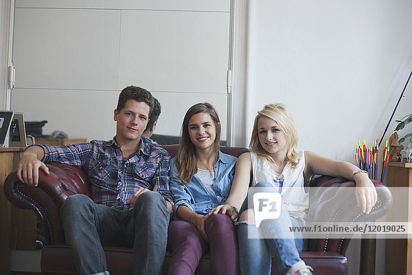 Porträt eines gutaussehenden Mannes  der schöne Freundinnen auf dem Sofa sitzt.