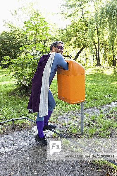 Reife Superhelden  die ihre Hände in den orangefarbenen Mülleimer legen.