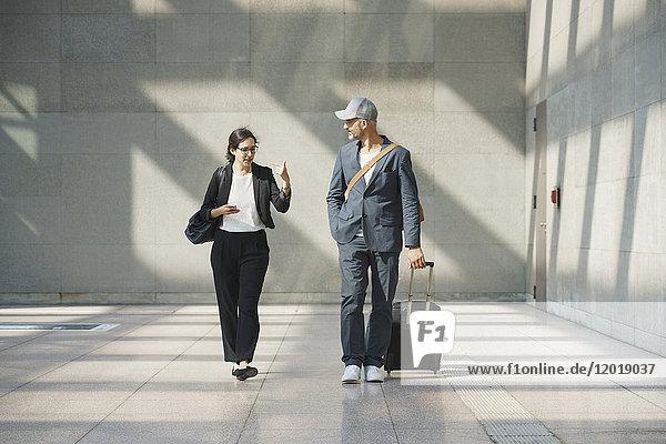 Geschäftskolleginnen und Geschäftskollegen im Gespräch beim Spaziergang am Flughafen