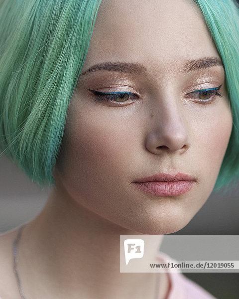 Nahaufnahme eines nachdenklichen Teenagermädchens mit grün gefärbten Haaren