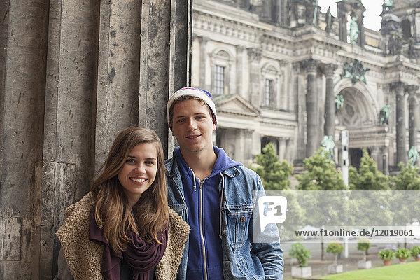 Porträt lächelnder junger Freunde an der Säule im Alten Museum gegen den Berliner Dom