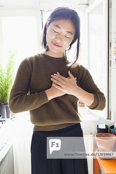 Lächelnde junge Frau mit Händen am Herzen  die am Fenster stehen.