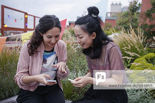 Glückliche weibliche Freunde  die Smartphones benutzen  während sie auf der Terrasse sitzen.