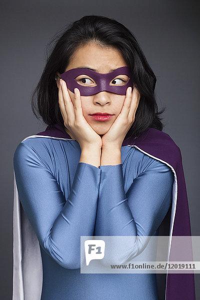 Junge Frau im Superheldenkostüm stehend mit Kopf in den Händen vor grauem Hintergrund