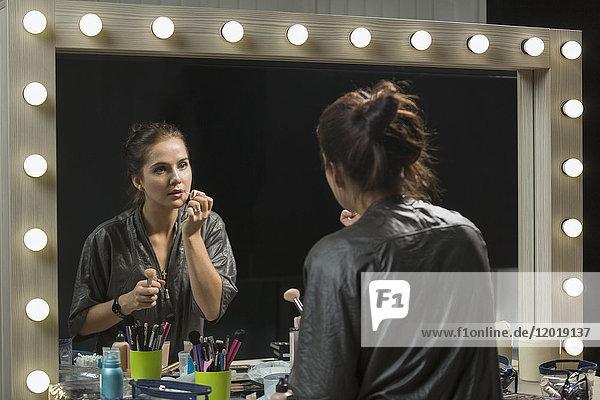 Schöne Frau mit Lipgloss vor dem Spiegel