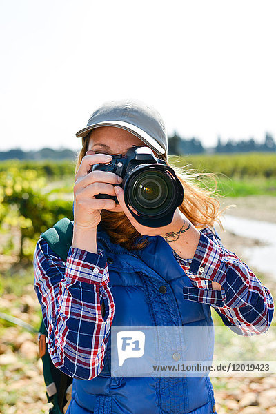 cheerful young woman hiking and taking pictures with her reflex single lens camera- Cepage Grenache  Chateauneuf du Pape  cotes du Rhone  France