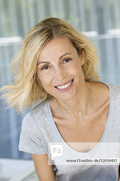 Portrait of a beauty smiling blonde woman with grey tee-shirt.