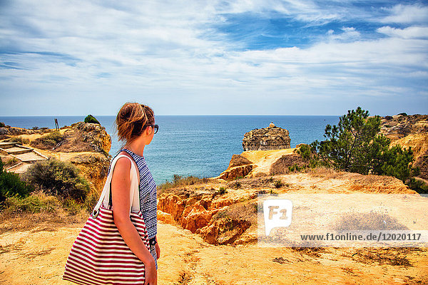Young woman observing the sea from the cliffs of the cove of Praia de Galapinhos  Setubal  Lisbon area  Portugal