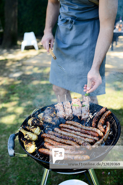 Close up of a barbecue grill with meat and sausages cooking during a summer garden party with people in background.