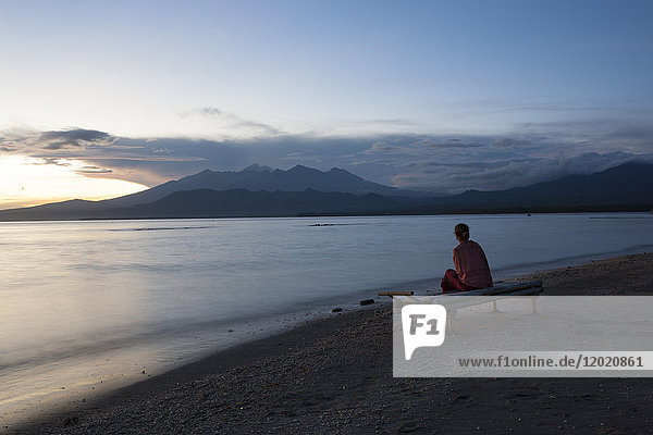 View of the volcano Gunung Rinjani at dawn with silhouette of a young woman seen from behind  Gili Air  Lombok  Indonesia